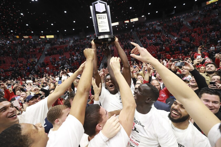 SDSU forward Joel Mensah holds up the Mountain West trophy as his celebrate after the Aztecs defeated New Mexico 82-59 at Viejas Arena on Feb. 11.