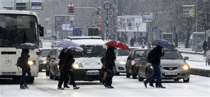 People cross a street covered with snow and ice in Skopje, Macedonia, on Tuesday, Dec. 11, 2012. The weather forecast predicts continuing snowfall and low temperatures for the next days in Eastern Europe. (AP Photo/Boris Grdanoski)