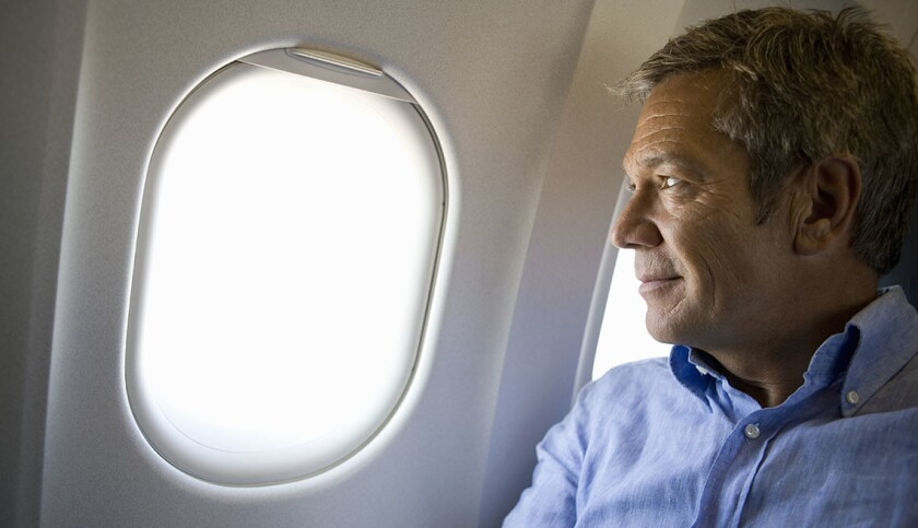 A male passenger on a plane looking through window