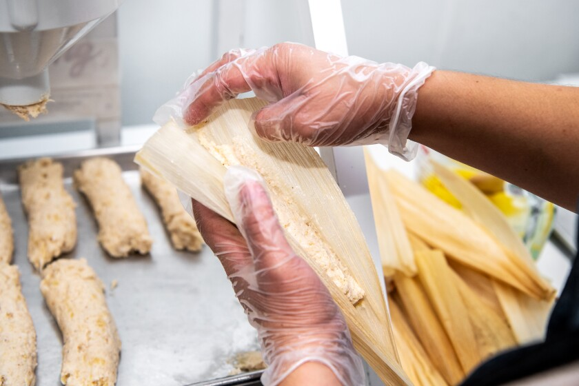 Vanessa Rodriquez constructs tamales at Artesano Tamaleria. The restaurant uses a machine that quickly and more accurately dispenses the masa, which traditionally is done by hand, saving them time.