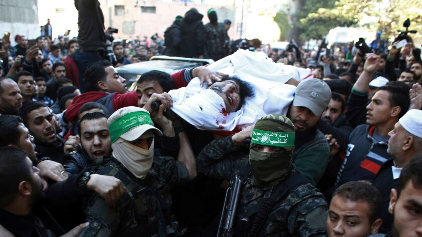 Palestinian mourners carry the body of Hamas militant Muhammed Al-Safadi, who was killed in an Israe