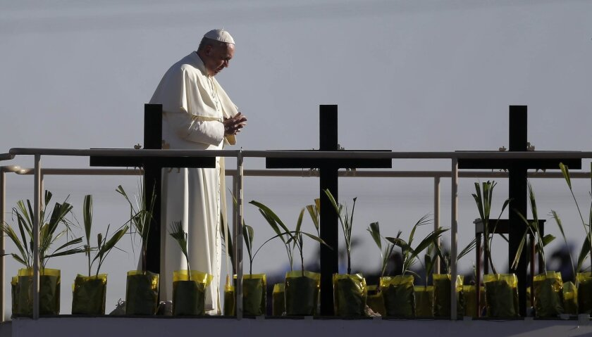 Pope Francis stands a platform near the U.S.-Mexico border fence along the Rio Grande, in Ciudad Juarez, Mexico, Wednesday, Feb. 17, 2016, as seen from in El Paso, Texas, Wednesday, Feb. 17, 2016. Francis made the sign of the cross and blessed hundreds of people gathered in El Paso. (AP Photo/Eric