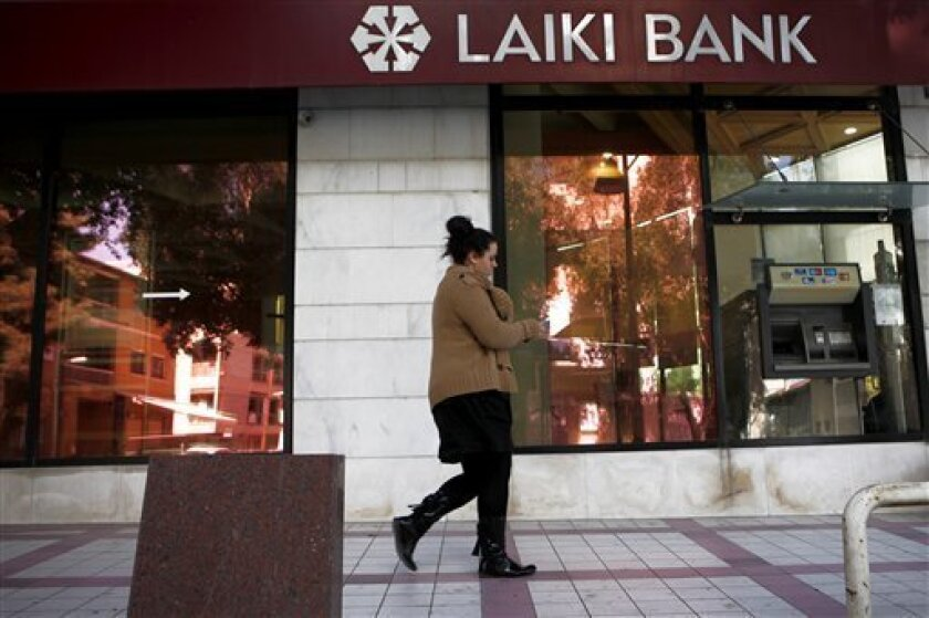 """A woman walks outside of Laiki Bank capital Nicosia, Cyprus, Wednesday, March 13, 2013. Cyprus' president Nicos Anastasiades says talks with international creditors for a much-needed rescue loan to keep the country from going bankrupt are paying off. Anastasiades urged patience, saying that it will soon become clear that """"hard work produces good results."""" (AP Photo/Petros Karadjias)"""