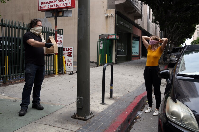 Eric Larkin hands over an order to Brittany Wright as she fastens her face mask outside downtown L.A.'s cavernous indie bookstore.