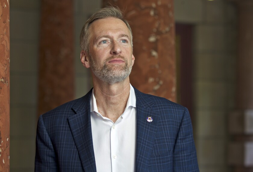 FILE - In this Aug. 5, 2019, file photo, Portland Mayor Ted Wheeler poses for a photo outside City Hall in Portland, Ore. Wheeler announced Thursday, March 11, 2021, he would seek $2 million in one-time funding from a reserve contingency account to invest in the Portland Police Bureau as well as other agencies and programs in hopes of slowing the city's rampant gun violence. (AP Photo/Craig Mitchelldyer, File)