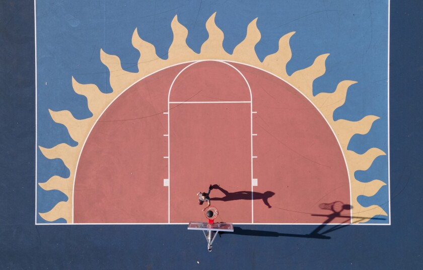 Cameron Wilson, 26, practices on the newly painted basketball courts at Colina Del Sol Park.