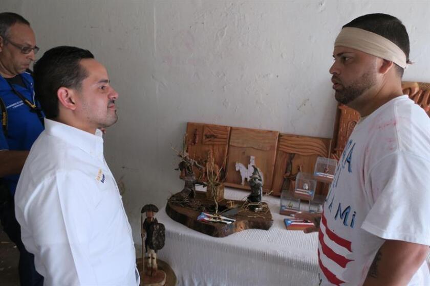 Fotografía del 20 de octubre de 2017, donde aparecen el secretario del Departamento de Corrección y Rehabilitación de Puerto Rico, Erik Rolón (i), conversando con el artesano preso Melvin Pastrana Collazo (d) en San Juan (Puerto Rico). EFE/Archivo