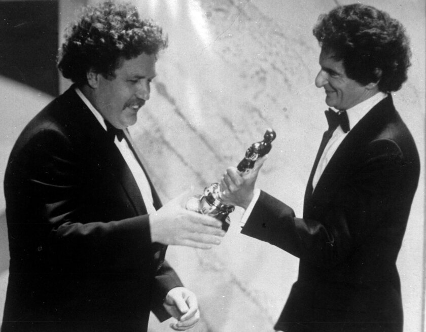 "FILE - In this March 29, 1982 file photo, British actor and writer Colin Welland, left, accepts an Oscar for the best screenplay from Jerzy Kosinski, during the 54th annual Academy Awards presentation, Los Angeles. Actor and writer Colin Welland, who famously told Hollywood ""the British are coming"""