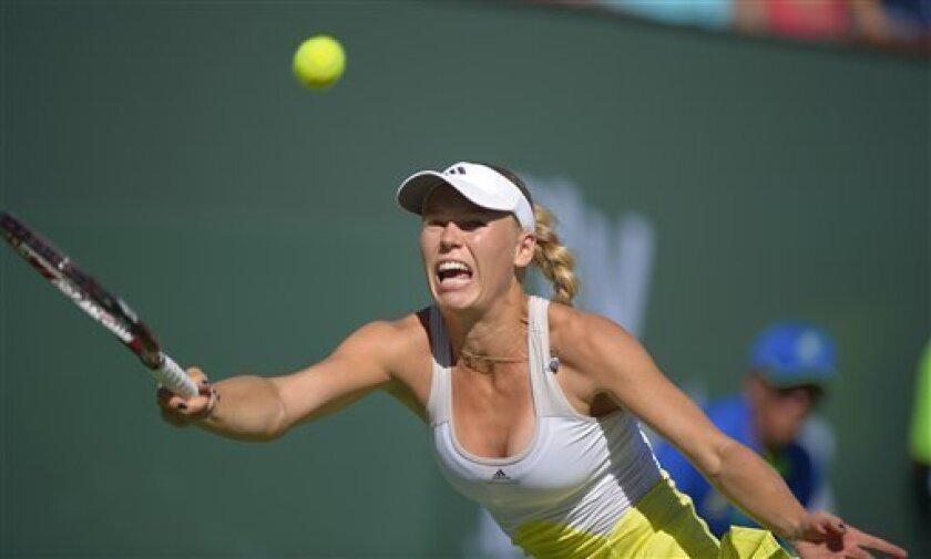 Caroline Wozniacki, of Denmark, returns a shot to Elena Vesnina, of Russia, during their match at the BNP Paribas Open tennis tournament, Monday, March 11, 2013, in Indian Wells, Calif. (AP Photo/Mark J. Terrill)
