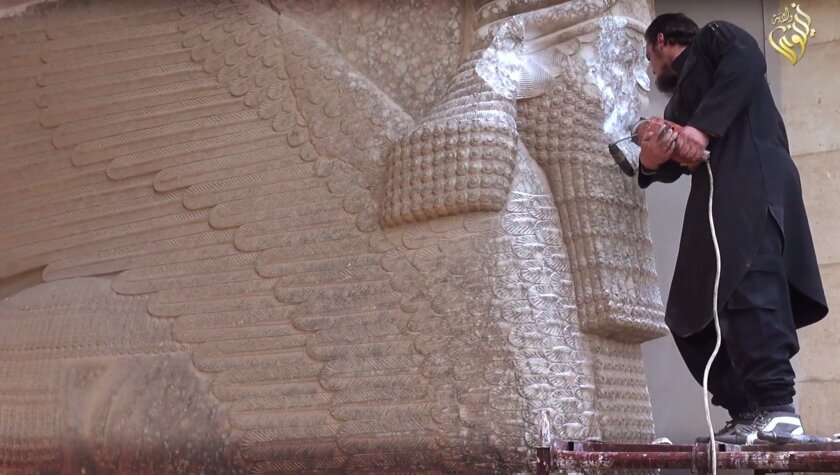 A militant affiliated with the Islamic State uses a power tool to destroy an Assyrian winged bull dating to the early 7th century BC at the gate of Nergal, near Mosul, Iraq.