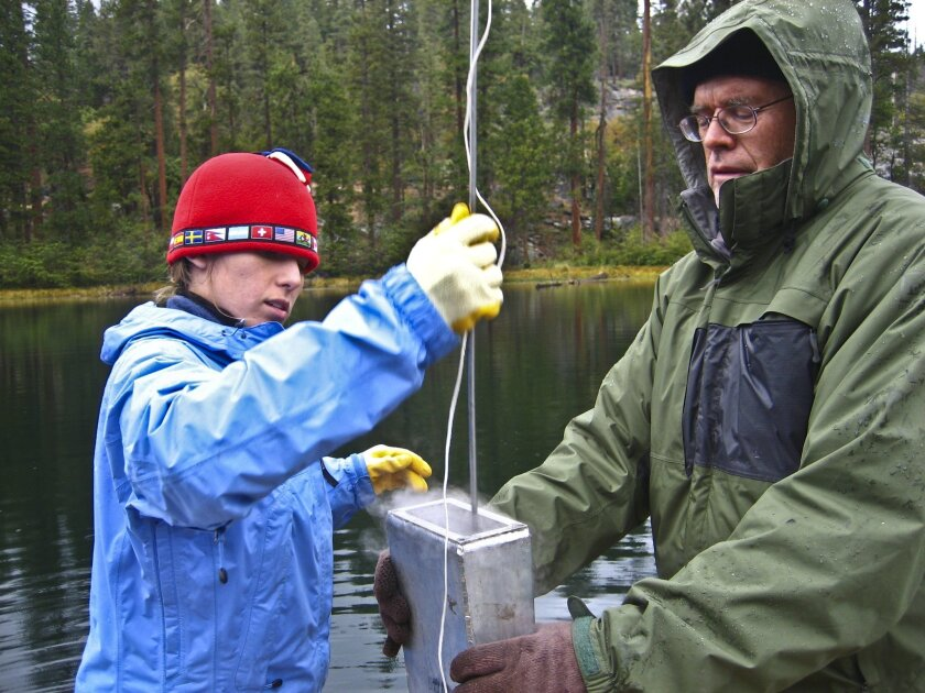 Graduate Student Lydia Roach assisted by Researcher Dan Cayan capture laminated sediments via freeze core from Swamp Lake located in Yosemite National Park in October 2007. COURTESY