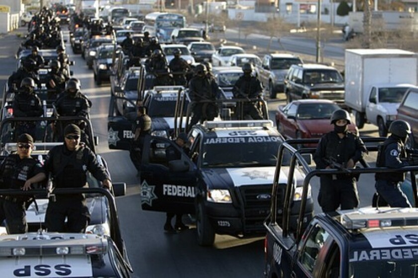 Federal police arrive in Mexico's most violent city, just across the border from El Paso, as part of a security buildup that is also to include thousands of additional soldiers.