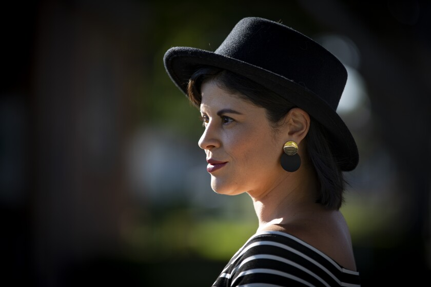 TV writer Judalina Neira poses in a black hat, black and white striped top, and black and gold earrings.
