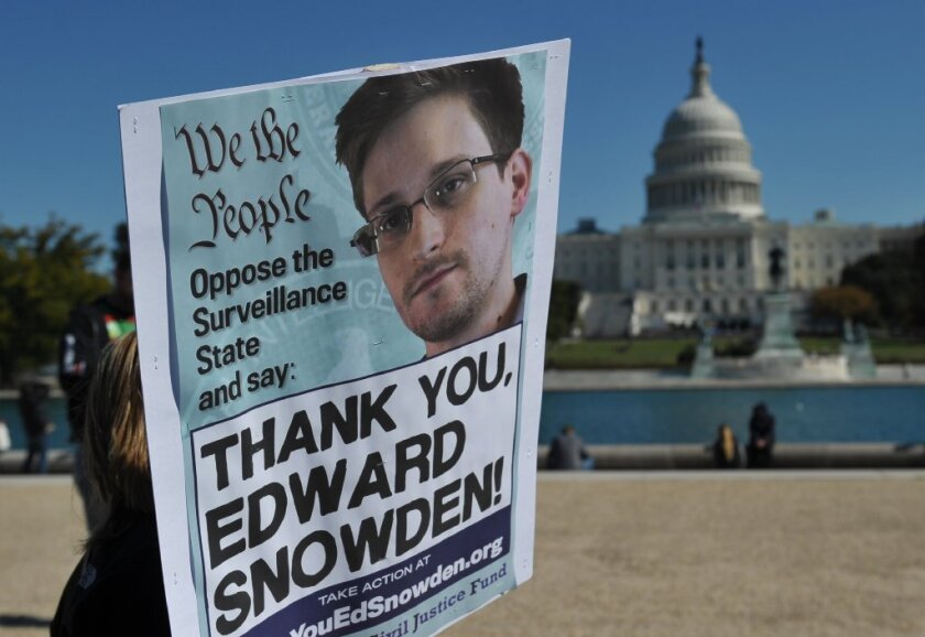 Demonstrators are seen holding placards supporting former U.S. intelligence analyst Edward Snowden.