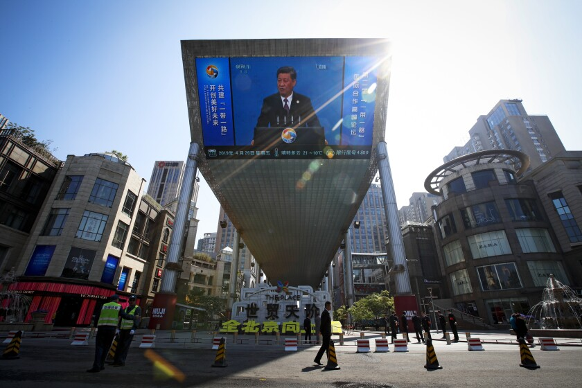 FILE - In this April 26, 2019, file photo, traffic warden and securities stand guard near a TV screen broadcasting live of President Xi Jinping's opening speech, outside a shopping mall in Beijing. Companies who do business with China walk a fine line to stay aligned with U.S. values such as freedom of speech and democracy while avoiding offending China, where they stand to make billions of dollars. (AP Photo/Andy Wong, File)