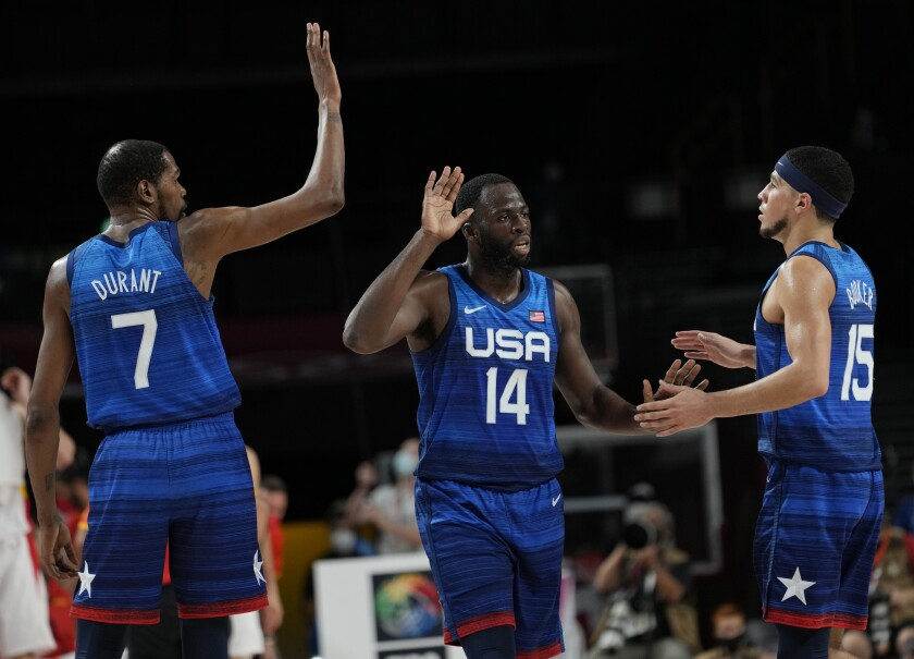 United States' Kevin Durant (7), left, and teammates Draymond Green (14) and Devin Booker (15) celebrate after scoring during men's basketball quarterfinal game at the 2020 Summer Olympics, Tuesday, Aug. 3, 2021, in Saitama, Japan. (AP Photo/Eric Gay)