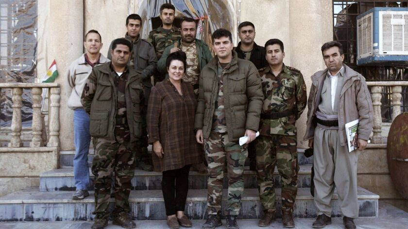 """Kelly Galindo stands with Kurdish soldiers while filming her documentary, """"26 Seconds,"""" in Iraq. The commander of the group assigned soldiers to watch over Galindo as she filmed."""