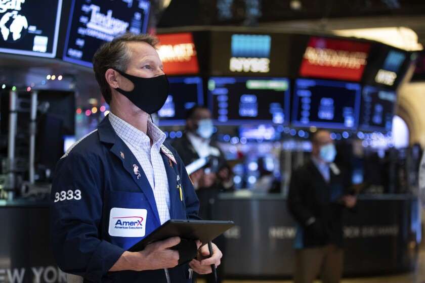 In this photo provided by the New York Stock Exchange, trader Robert Charmak works on the floor.