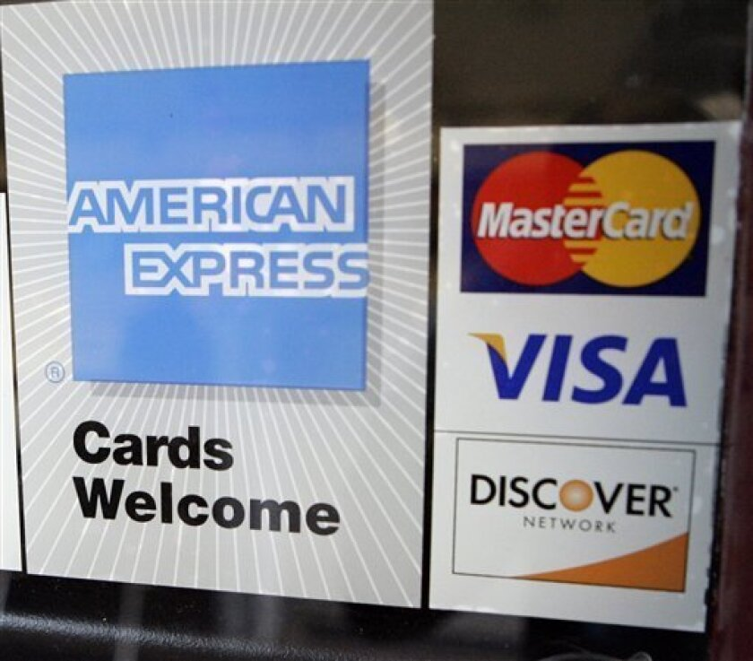 FILE - This July 30, 2008, file photo, shows credit card stickers posted at a bowling alley in Palo Alto, Calif. Credit-card companies are rushing to raise rates and tack on extra fees ahead of a law slated to take effect Feb. 22 that is supposed to limit such moves in the future. In some cases, rates are doubling to as high as 30 percent or more, even for people who pay their bills on time. (AP Photo/Paul Sakuma)