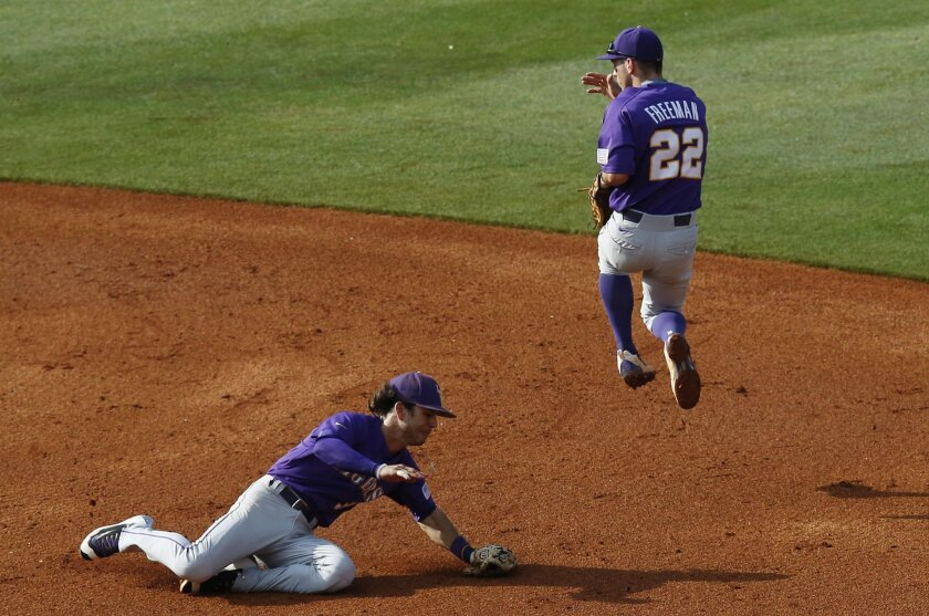 LSU infielder Cole Freeman, right, jumps out of the way as Kramer Robertson dives and fields a ground ball against Florida during the second inning of a Southeastern Conference NCAA college baseball tournament game at the Hoover Met, Saturday, May 28, 2016, in Hoover, Ala. (AP Photo/Brynn Anderson)