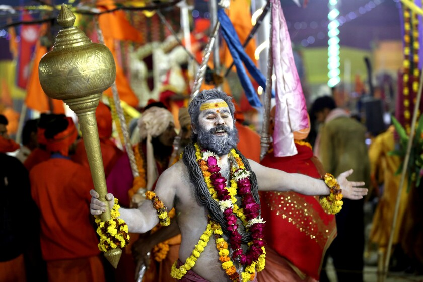 In this Tuesday, Jan.15, 2019, file photo, a Hindu holy man dances holding a mace as he arrives for