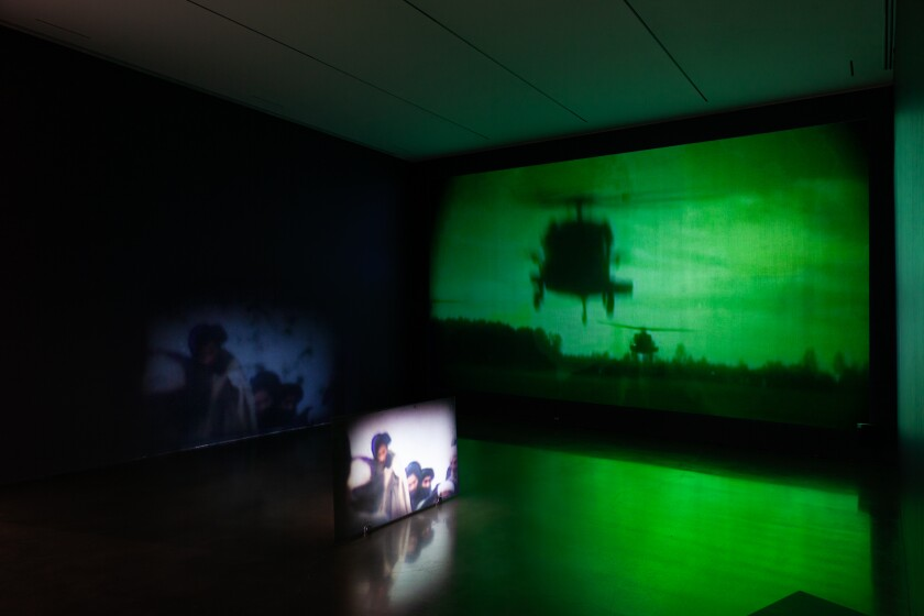 A dim gallery features a projection of a military helicopter bathed in green light and a monitor showing male figures