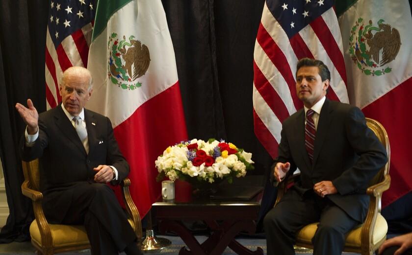 Joe Biden sits with Enrique Peña Nieto in front of U.S. and Mexican flags