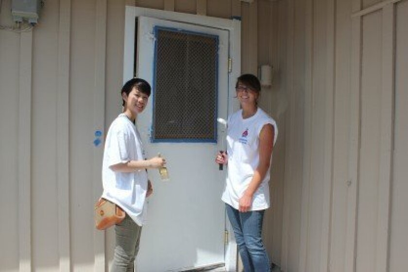 Interact Club students Tessa Lowe of La Jolla High School and Emily Halaka of University City High School paint a door at the rear of the police storefront.