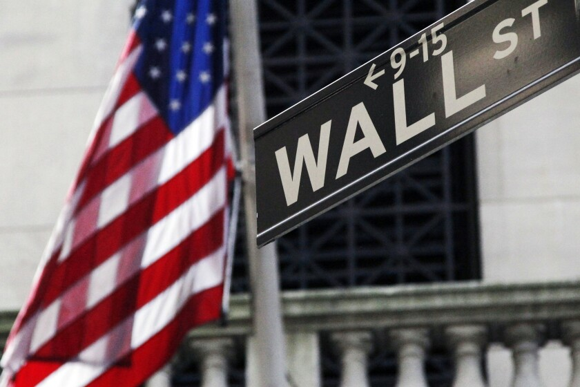 The American flag is left of a Wall Street sign outside the New York Stock Exchange.
