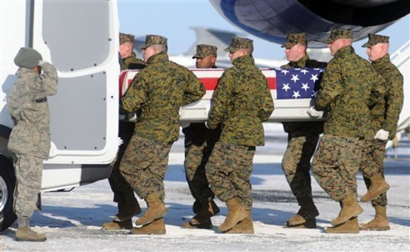 A Marine carry team loads a transfer case containing the remains of Marine Sgt. David Smith Sunday, Jan. 31, 2010 at Dover Air Force Base, Del. According to the family, Smith died of injuries he suffered in an attack last week in Afghanistan. (AP Photo/Steve Ruark)