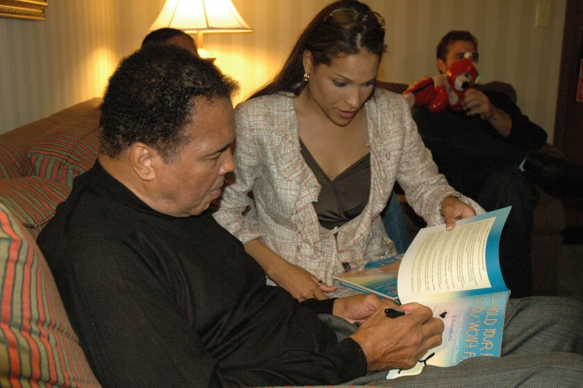 Muhammad Ali sits next to his daughter Rasheda Ali as he signs his name in a copy of her book