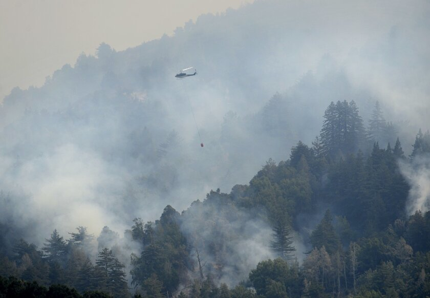 A helicopter flies in to make a water drop while fighting a wildfire on a ridge above Rancho San Carlos in Carmel Valley, Calif., Saturday July 30, 2016. Fire officials say a wildfire burning near California's dramatic Big Sur coast has destroyed dozens homes and is threatening over a 1,000 more. (