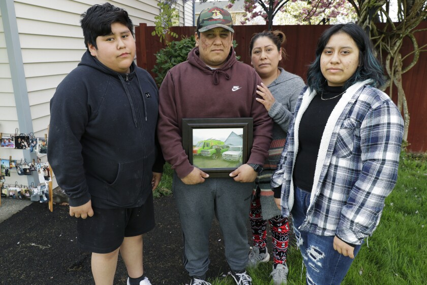 FILE - In this April 23, 2020 photo, Isaac Lopez, 19, second from left, holds a photo of his father, Tomas Lopez, as he poses for a photo with his mother, Antonia, second from right; his brother, Elias, 12, left; and his sister Elda, 16, right, at their home in Pacific, Wash. Tomas, 44, who died of COVID-19 on April 2, was a beloved fixture wherever he sold tacos from his family's bright green taco truck. The passage of a milestone — 100,000 lives lost due to the coronavirus in the United States — has brought attention to how news organizations are trying to tell the stories behind the numbers. (AP Photo/Ted S. Warren)