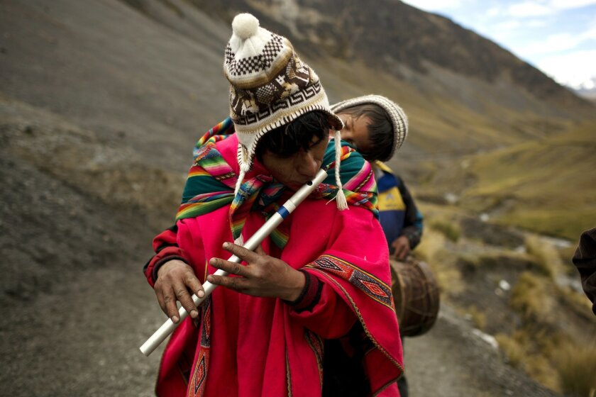 In this May 24, 2016 photo, a pilgrim carrying his son on his back, plays a traditional Andean flute known as a quena, as he walks the five miles to the Sanctuary of the Lord of the Qoyllur Rit'i, to take part in the syncretic festival of the same name, translated from the Quechua language as Snow