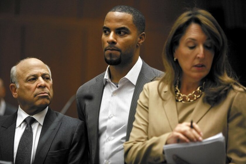 Flanked by attorneys Leonard Levine, left, and Blair Berk, former NFL player Darren Sharper appears in court in Los Angeles on charges of drugging and sexually assaulting women he allegedly met at a West Hollywood nightclub. Prosecutors say he's also suspected of assaulting women in three other states.