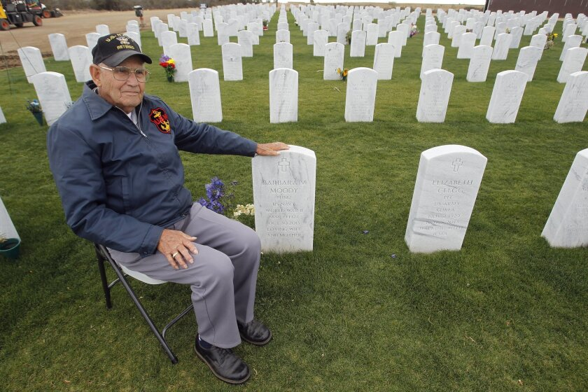 Raymond Moody, who served in the Navy in World War II, Korea, and Vietnam, sits next to the grave of his wife Barbara Moody, who also served in the Navy, at the Miramar National Cemetery in San Diego on Thursday. Moody visits his wife's grave most everyday.