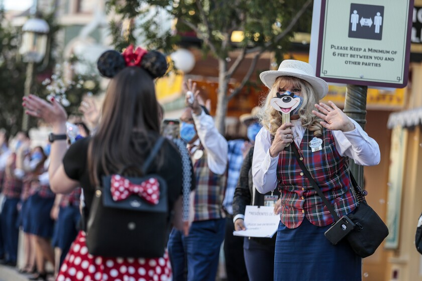A Disneyland worker greets visitors.