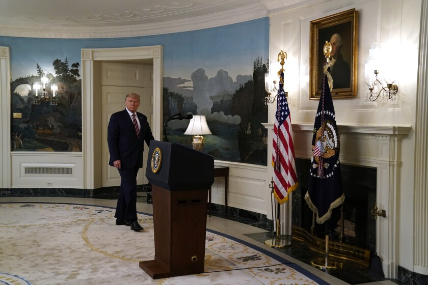 President Trump enters the White House Diplomatic Room on Wednesday, where he defended his downplaying of the coronavirus.