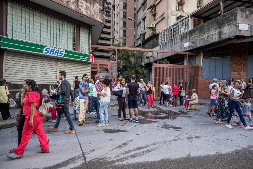 """Un grupo de personas permanece en la calle luego de que se registrara un sismo hoy, martes 21 de agosto de 2018, en Caracas (Venezuela). Los venezolanos se vieron hoy estremecidos por un fuerte sismo de magnitud 6,3 con epicentro en el """"sureste de Yaguarapano"""" en el oriente del país, de acuerdo con la Fundación Venezolana de Investigaciones Sismológicas (Funvisis), aunque el Servicio Geológico de EE.UU. reporta una magnitud de 7,0."""