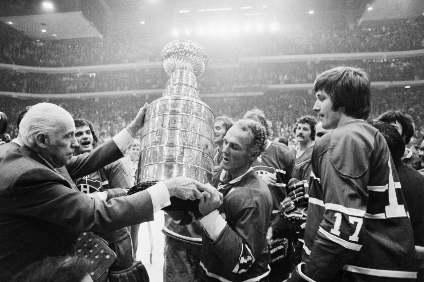 NHL president Clarance Campbell hands the Stanley Cup to Canadiens captain Henri Richard in 1973.