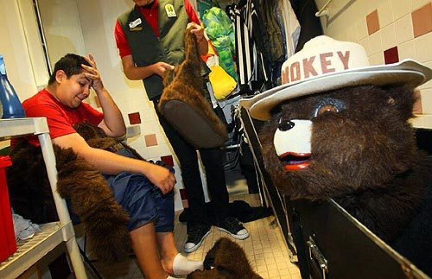 Andrew Garza, 16, a high school senior from Santa Ana, wipes his brow after a session dressed as Smokey Bear at the Discovery Science Center in Santa Ana. Helping Garza pack up the bulky suit is Juan Plascencia, who guides him in crowds because of the costume's limited visibility.