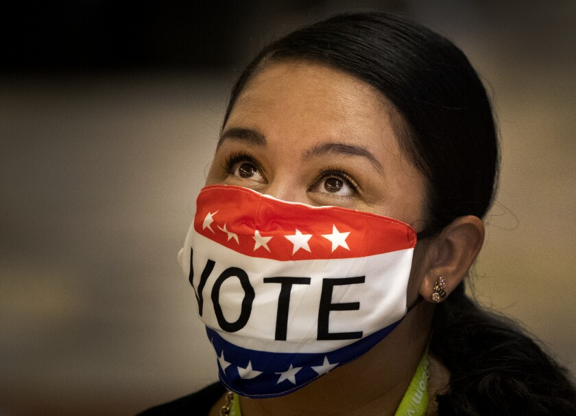 Election worker Melissa Balderas wears a topical mask while assisting early voters Monday at the Honda Center in Anaheim.