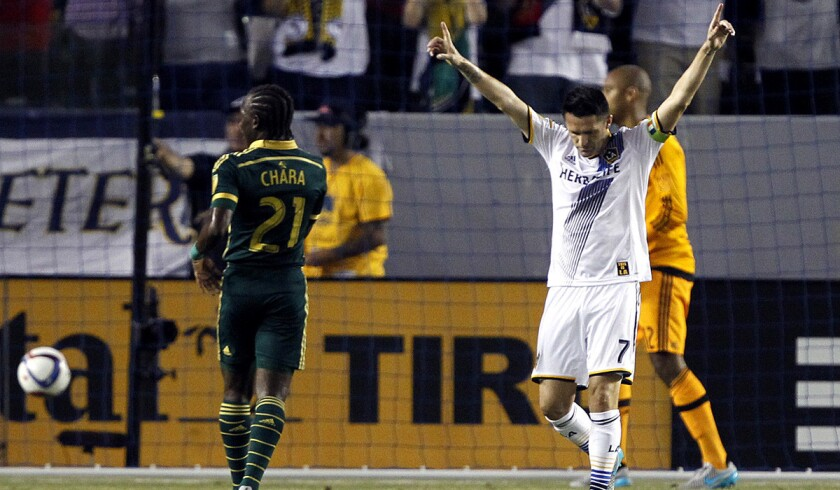 Los Angeles Galaxy forward Robbie Keane reacts to scoring on a penalty kick past Portland Timbers goalkeeper Adam Kwarasey, right, as midfielder Diego Chara, left, looks on during the first half on June 24. Galaxy won, 5-0.