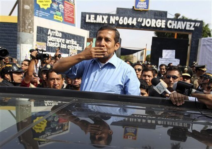 Presidential candidate Ollanta Humala waves to voters outside a polling station in Lima, Peru, Sunday April 10, 2011. Humala was waiting on his wife, Nadine Heredia, who was inside the polling station casting her vote. Humala, a former military officer, who promises to favor the poor by redistributing Peru's mineral wealth, was expected to win the most votes in Sunday's presidential elections but fall far short of the outright majority needed to avoid a runoff. (AP Photo/Juan Diego Contreras)