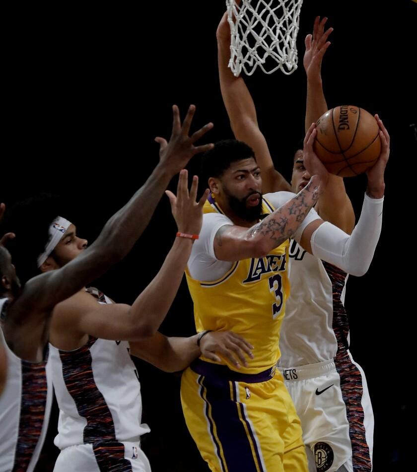 Lakers forward Anthony Davis draws a crowd of Nets during the fourth quarter of a game March 10 at Staples Center.