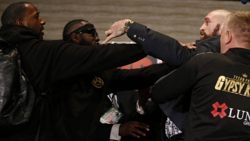 Deontay Wilder, second from left, and Tyson Fury, second from right, scuffle as they exchange words while facing each other at a news conference.