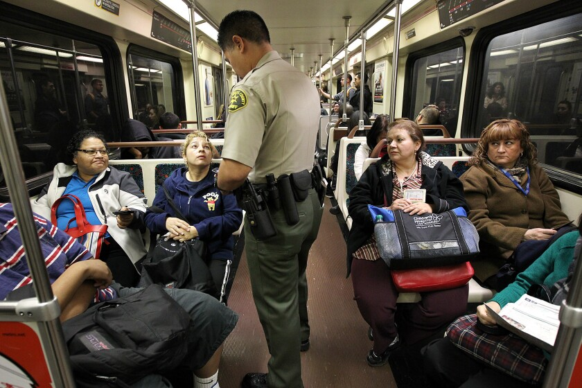 A Los Angeles County Sheriff's Department deputy performs a fare check during a patrol through a Metro train in downtown Los Angeles.