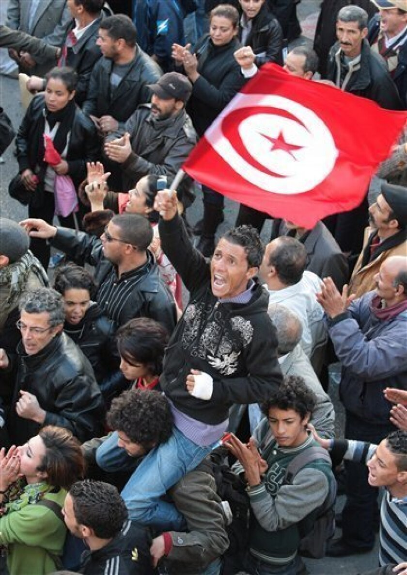A member of the leftist UGTT union holds a Tunisian flag during a rally to commemorate the 1955 assassination of a historic member when they were attacked by the League for Protection of the Revolution, Tuesday, Dec. 4, 2012 in Tunis. League members are considered to be close to the Ennahda Party, which dominates Tunisia's post-revolution coalition government. (AP Photo/Amine Landoulsi)