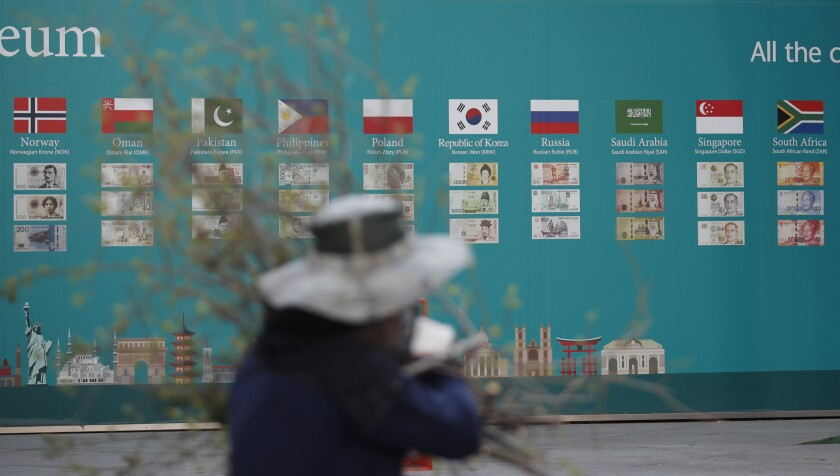 A worker walks past a bank's advertisement in Seoul on March 24.