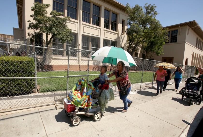 Padres de familia recogen a sus hijos en la escuela Rowan Avenue, en el Este de Los Ángeles. Este fue uno de los tres centros escolares con cercas metálicas que instaló el LAUSD para alejar a los estudiantes del suelo contaminado que ha causado la planta Exide en el sureste del condado.